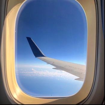 飛行機の窓から顔を出している  自動的に生成された説明