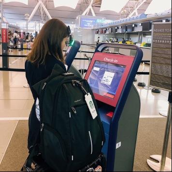 空港で荷物を持っている女性  自動的に生成された説明